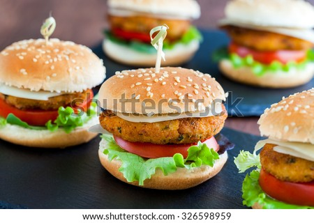 Extreme close up of multiple Appetizing mini chicken burgers. Small burgers in row for catering service.