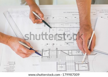 Extreme close-up of several hands working on blueprints in the office - stock photo