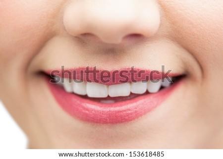 Extreme close up on beautiful white smile wearing pink lipstick - stock photo