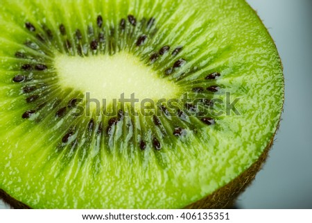Extreme close up on black seeds in juicy green kiwi fruit slice with orange pieces obscured in background - stock photo