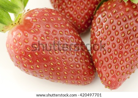 Extreme close up on glossy skin and seeds on three fresh strawberries over white background - stock photo