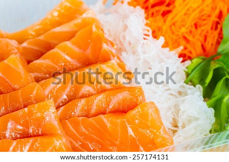 extreme close-up orange salmon fish cut with slices with vegetables