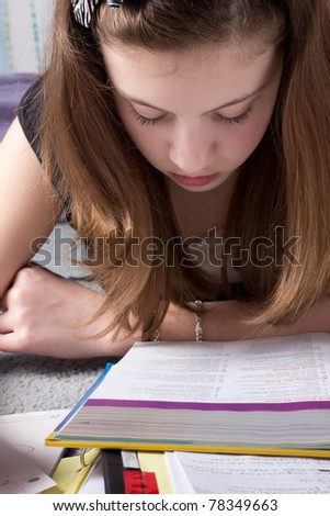 Extreme closeup of a cute girl in deep concentration as she studies - stock photo