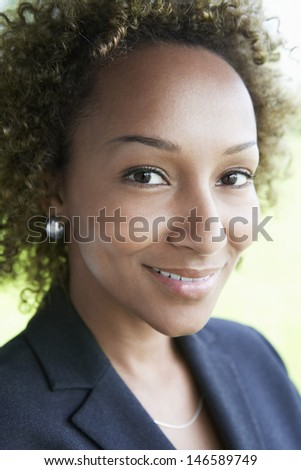 Extreme closeup of a smiling young businesswoman outdoors