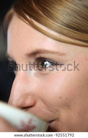 Extreme closeup of a woman drinking tea - stock photo
