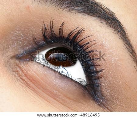 Extreme closeup of a woman's eye, eyelashes and eyebrow - stock photo