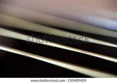 Extreme closeup of acoustic guitar strings, mostly unfocused to simulate vibrations - stock photo