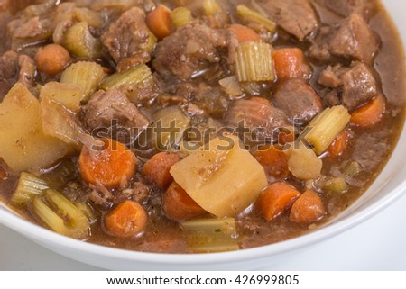 Extreme closeup of beef stew in white bowl with white plate beneath as background. - stock photo