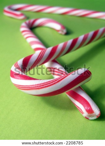 Extreme closeup of candy canes on green background.