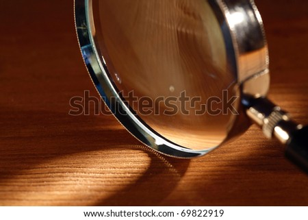 Extreme closeup of magnifying glass standing on wooden surface with beam of light - stock photo