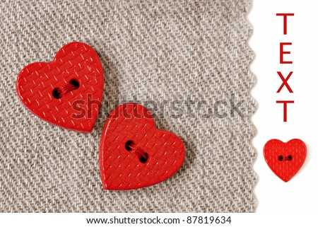 Extreme closeup of tiny heart shaped buttons sewn on natural cotton fabric with white background and copy space. - stock photo
