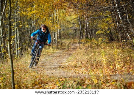 Extreme cyclist riding on mountain bike in autumn colorful deciduous forest - stock photo