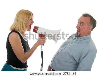Extreme domestic argument with wife shouting commands through a megaphone at her fearful husband. - stock photo