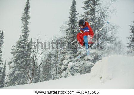 Extreme downhill skier skiing in the snow in the pine and spruce forest. Descent in Sheregesh, Russia