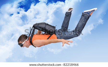 Extreme flight man with a parachute in the clouds - stock photo