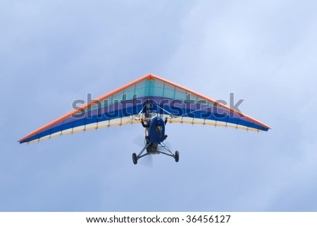 Extreme flight on deltaplane in a blue sky - stock photo