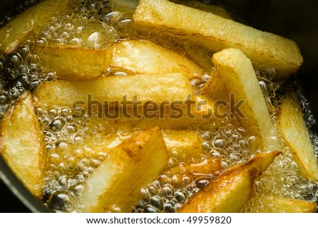 Extreme Macro of chips/fries cooking in a pan. - stock photo