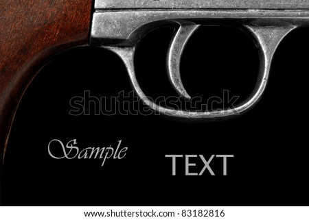 Extreme macro of vintage revolver trigger on black background with copy space.  Conceptual image for 'pulling the trigger' or initiating action.  (gun is replica of army  revolver from U.S. civil war) - stock photo