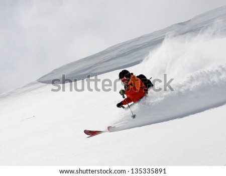 Extreme skier blasting down a slope with a large cornice in the background. - stock photo