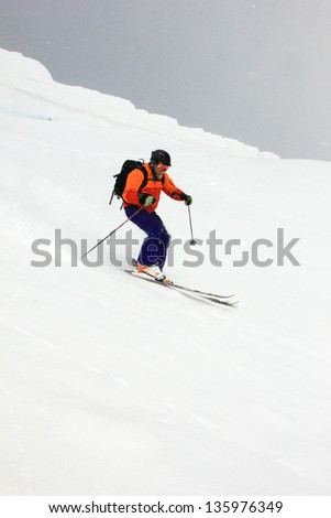 Extreme skier charging down a rugged slope. - stock photo