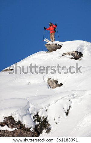 Extreme skier stands on the high peak and preparing to go down
