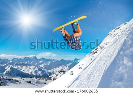 Extreme snowboarder jumping high in the air - stock photo