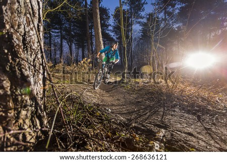 extreme sports on a off road trail in the forest with an ATB in the late afternoon - stock photo