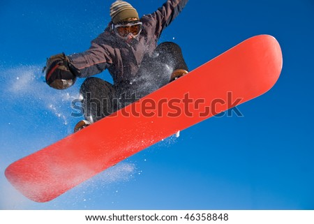Extreme sports: snowboarder flying in air, snow crystals flying everywhere