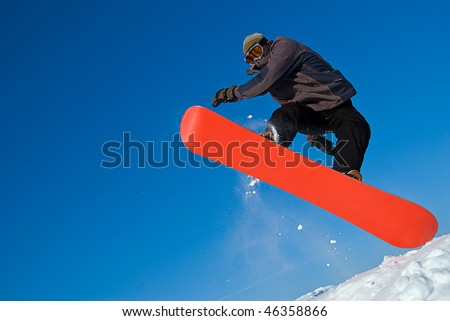 Extreme sports: snowboarder flying in air, snow crystals flying everywhere - stock photo