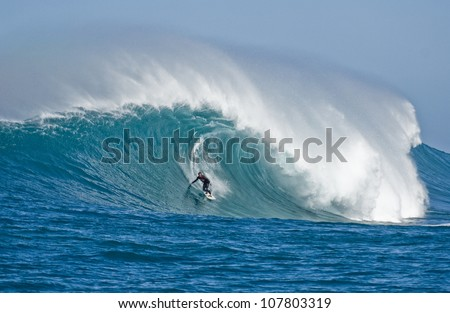 Extreme surfers riding some giant waves - stock photo