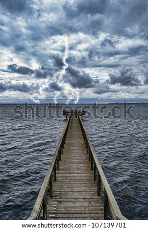 Extreme weather conditions from an approaching storm viewed from a wooden pier on the coast. - stock photo