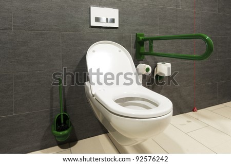 extreme wide angle of a white toilet for disabled pesrons - stock photo