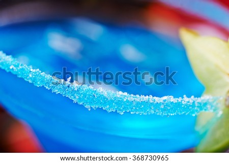 extremely close up of  bright refreshing cocktails: blue margarita on a table in a restaurant with creative decoration of salt on the edge of the glass with fruit slices and berries. soft focus - stock photo