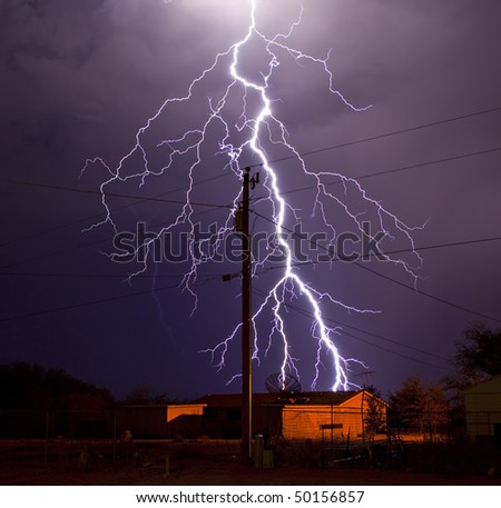 Extremely detailed lightning bolt behind electric utility pole - stock photo