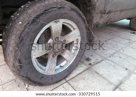 Extremely dirty SUV wheel after driving heavy off-road in the rain
