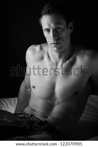 Extremely fit and handsome young caucasian adult man sitting on a bed against a dark wall wearing blue jeans and without a shirt. Black and White. - stock photo