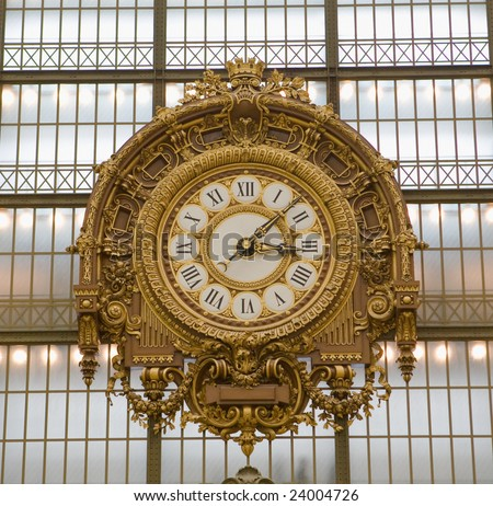 Extremely large, golden colored clock inside Musee d'Orsay Museum in Paris, France, which contains contemporary artwork - stock photo