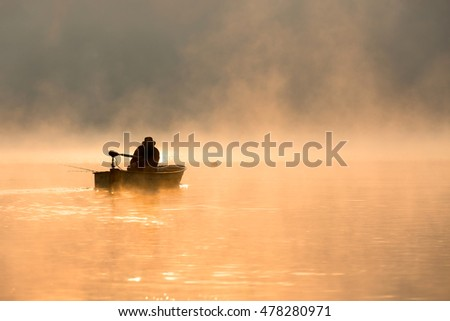 Exuding a fisherman in the morning in the fog backlit by the sun.