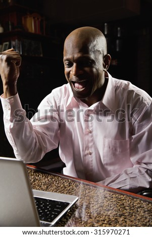 Exultant guy wearing pink shirt whooping while sitting with laptop at coffee beans covered table in dark room - stock photo