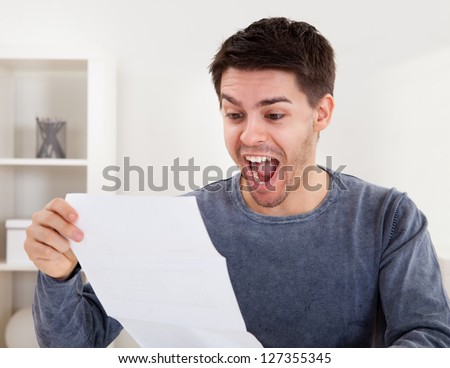 Exultant young man cheering at good news he has just received in a document that he is reading - stock photo