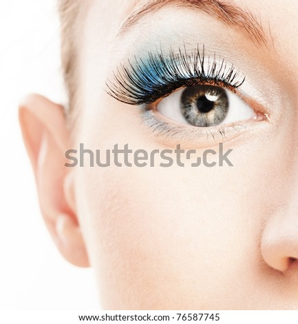 Eye and nose of beautiful young woman close up, soiled by green cosmetics. - stock photo