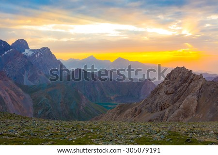 Eye catching highland dusk.  Beautiful eye catching mountain scenery with rising sun sunbeams passing throw clouds green grass and flowers on foreground brown and red peaks and ridges on background - stock photo