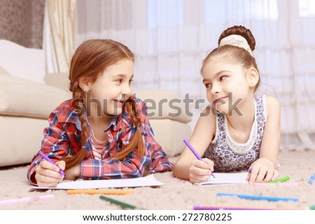 Eye contact. Cute smiling girls lying on carpet and drawing with help of colorful crayons and looking to each other