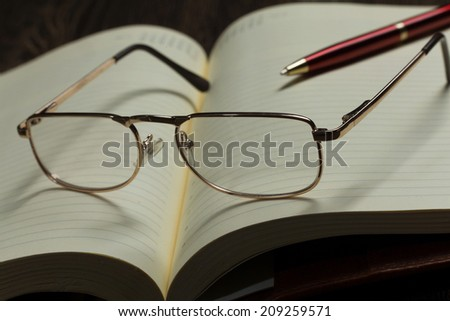 Eye glasses lying on opened blank notepad