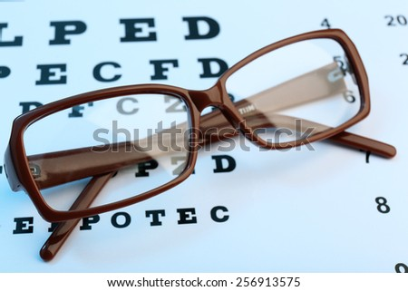 Eye glasses on eyesight test chart background - stock photo