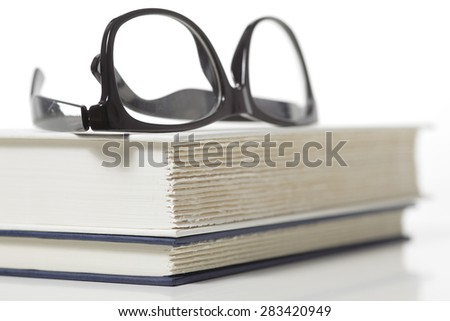 eye glasses on stacked books - stock photo