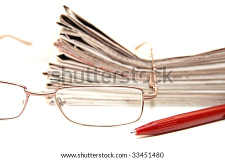 Eye glasses with pen and newspaper - stock photo