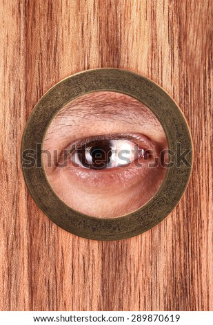 Eye is looking through peephole - stock photo