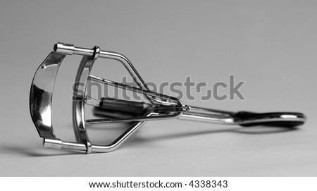 eye lash curler on a grey background