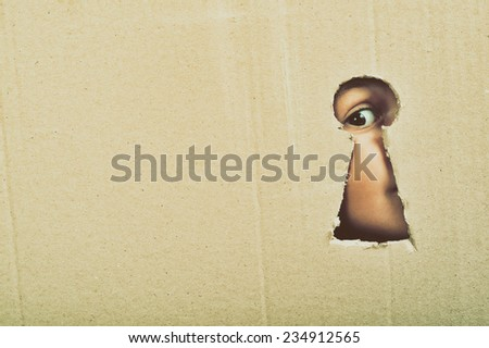 Eye looking through a conceptual keyhole on cardboard, close up - stock photo